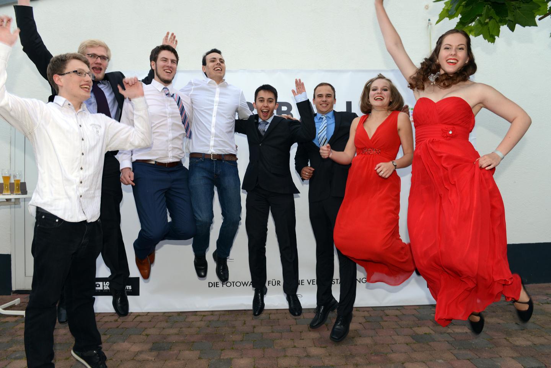 Gruppenbild mit Sprung. Alle Personen springen gleichzeitig in die Luft.