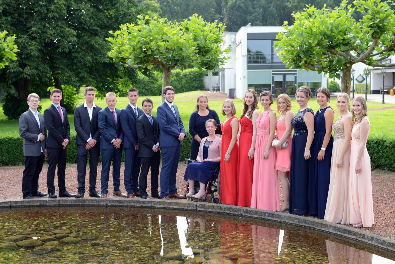 Gruppenbild bei einem Abiball mit der ganzen Klasse vor einem Brunnen.