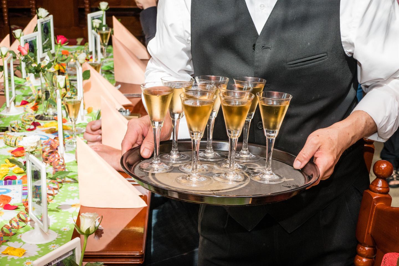 Auf diesem Partyfoto bringt der Kellner den Sekt auf einem Tablett.