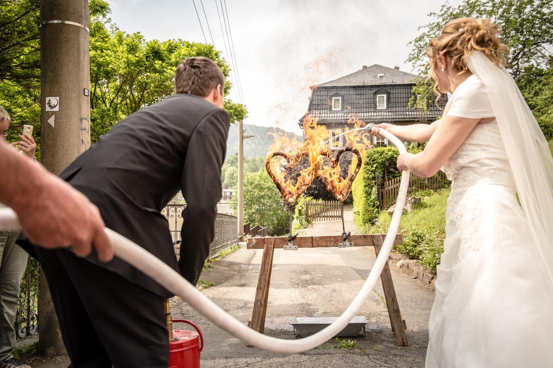 Tolles Hochzeitsfoto! Das Brautpaar löscht mit einem Feuerwehrschlauch ein brennendes Herz.
