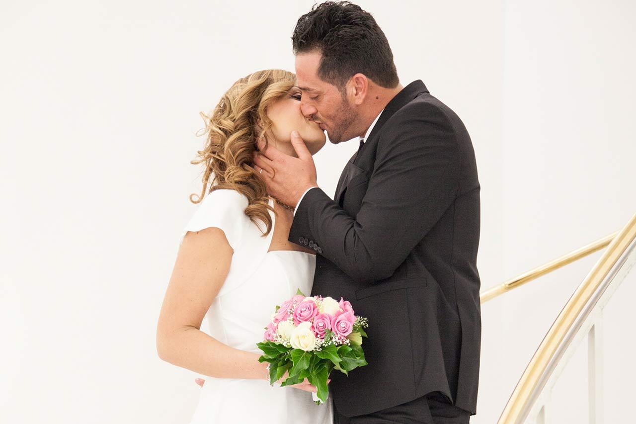 Der Bräutigam und seine Braut küssen sich auf der Treppe im Standesamt.