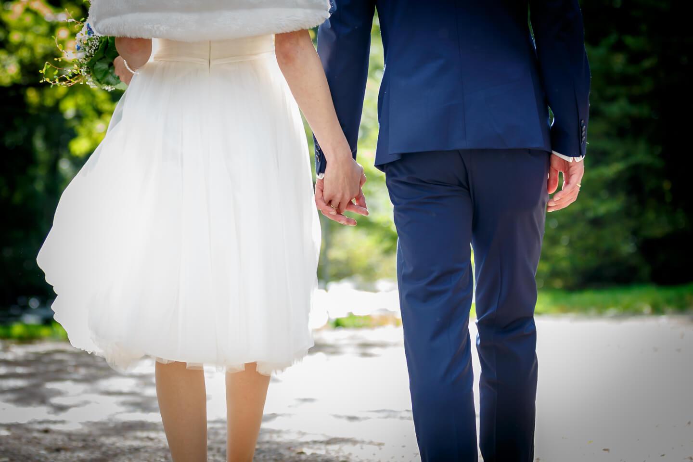 braut und bräutgam laufen hand in hand einen weg entlang