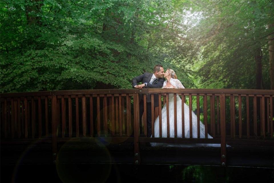 Braut und Bräutigam auf einer Holzbrücke im Wald.