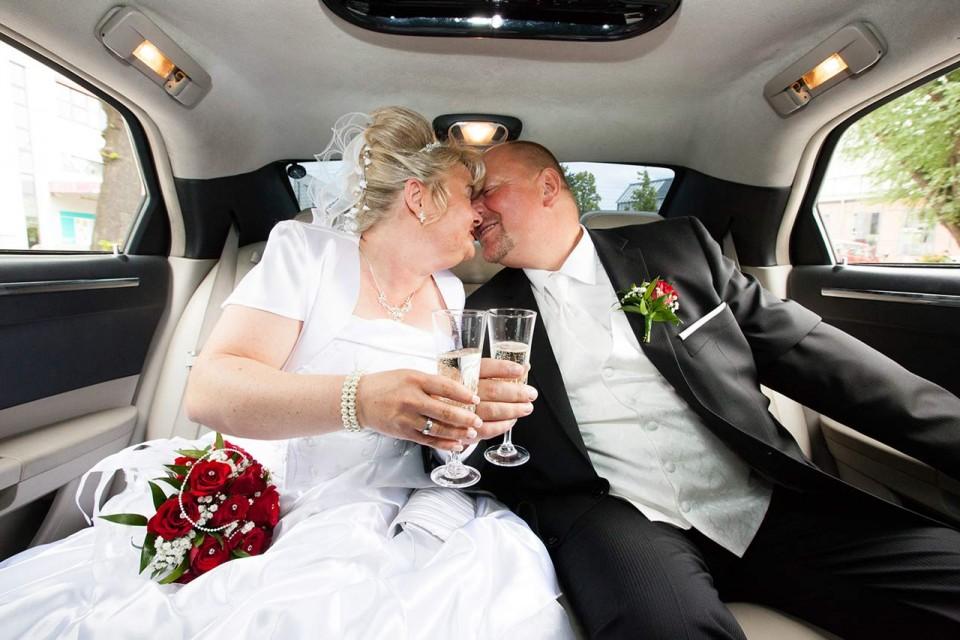 Braut und Bräutigam küssen sich in einer Stretch Limo.