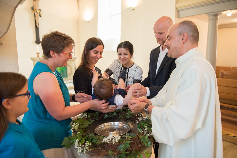 Kind wird am Taufbecken getauft