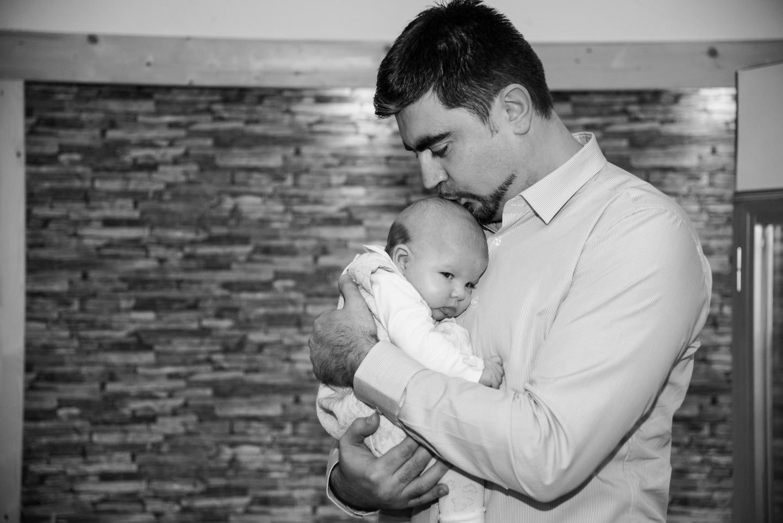 Der Vater küsst sein Kind auf den Kopf. Das Tauffoto ist in schwarz weiß.
