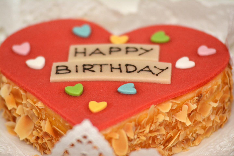 Ein Happy Birthday Geburtstagskuchen in Form von einem Herz.