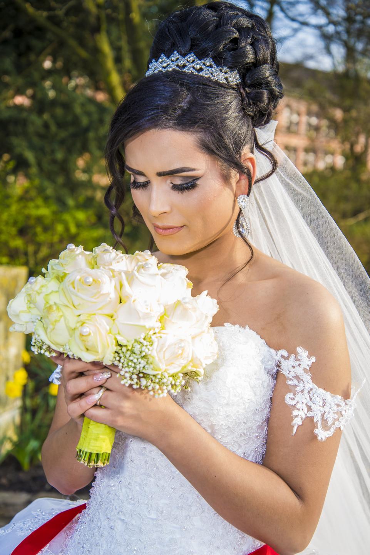 Wunderschöne Braut im weißen Brautkleid und mit Brautstrauß.