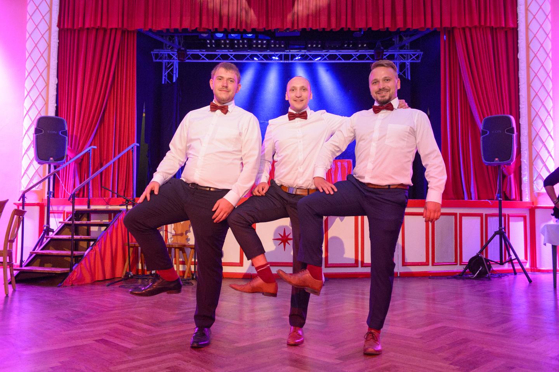 Tanzeinlage vor der Bühne von drei Männern auf einer Party.