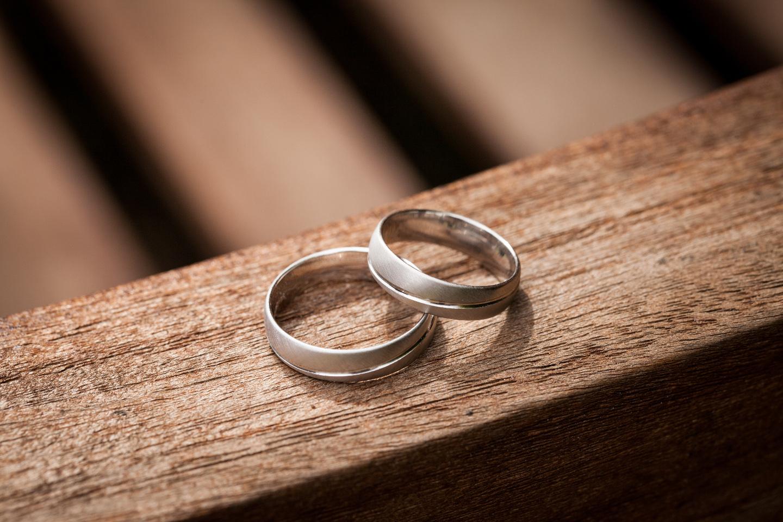 Ringfoto von Hochzeitsringen auf einem braunen Holztisch.
