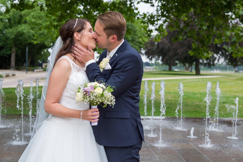 Der Hochzeitsfotograf von MeinPartyfotograf fotografiert das Brautpaar vor einem Brunnen.