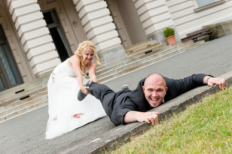 Super lustiges Hochzeitsfoto. Die Braut zieht den Bräutigam zum Altar.