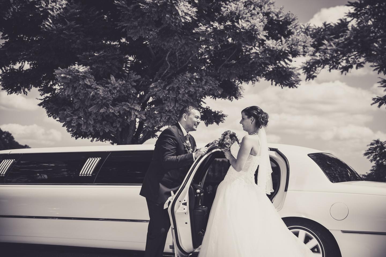Wunderschönes Hochzeitsfoto in schwarz weiß und mit einer Limousine im Hintergrund.