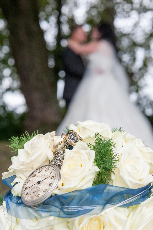 Wunderschönes Hochzeitsfoto mit Brautstrauß im Vordergrund und unscharfem Brautpaar im Hintergrund.