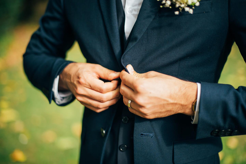 Anzug zukuepfen im Freien vor der Hochzeit