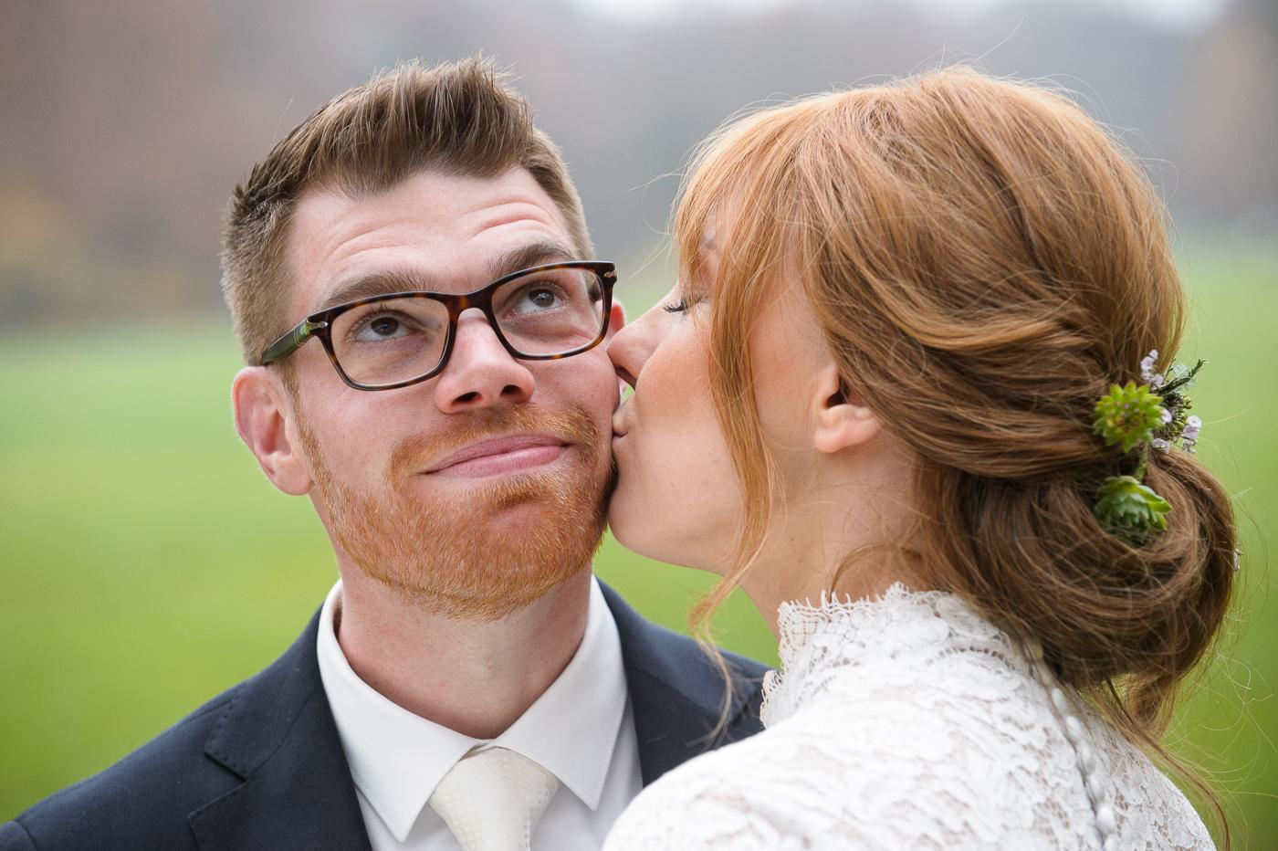 Braut küsst Bräutigam im Englischen Garten