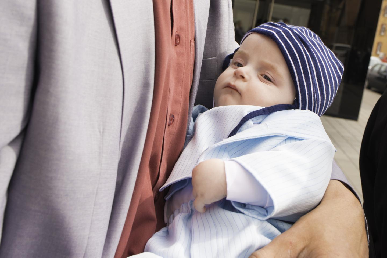 Baby liegt nach der Taufe in den Armen seines Vaters.