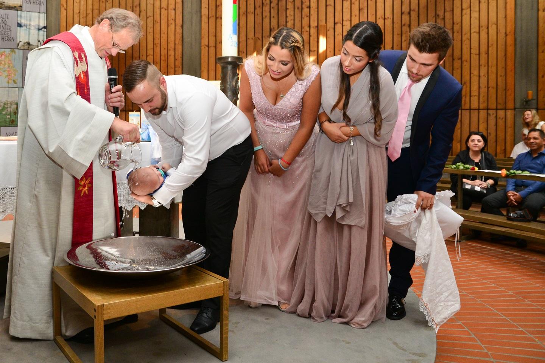Familie waehrend der Taufe in der Kirche