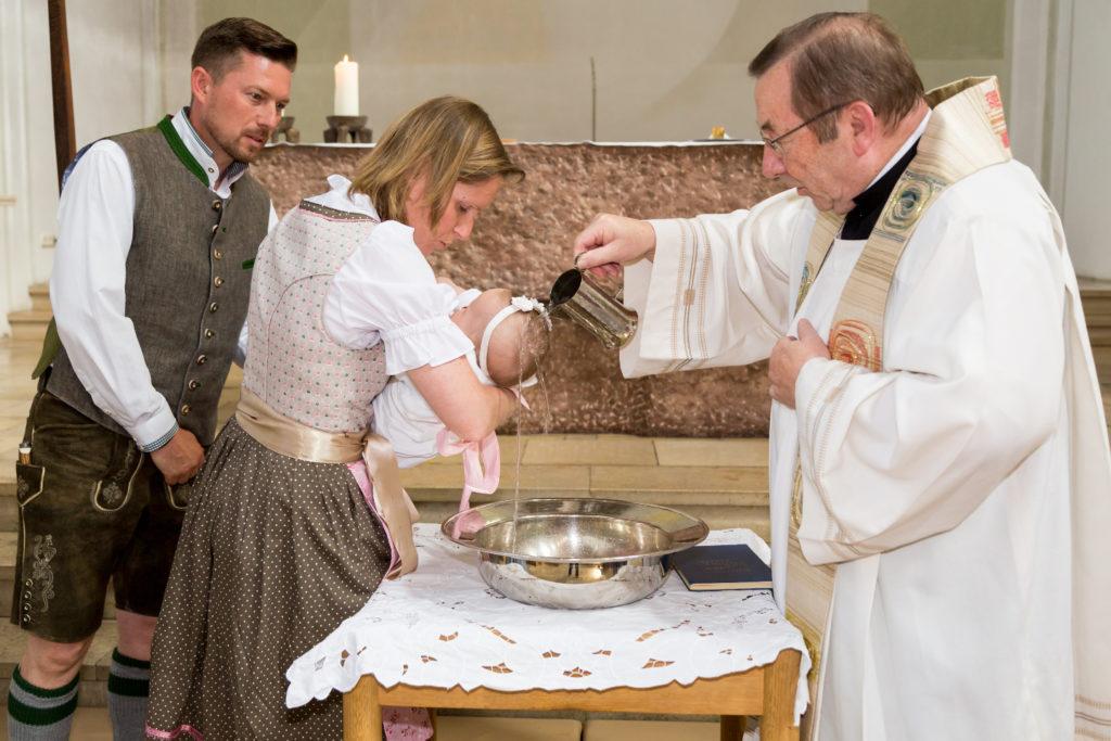 Familie in Tracht bei der kirchlichen Taufe