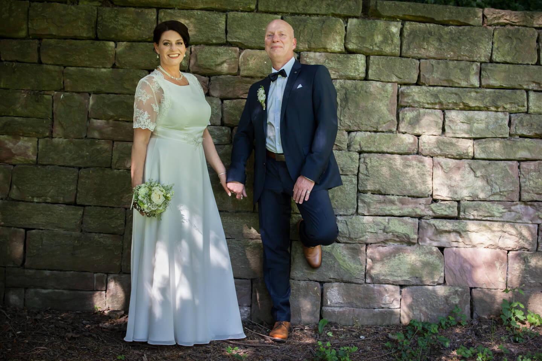 Hochzeitspaar lehnt an Mauer