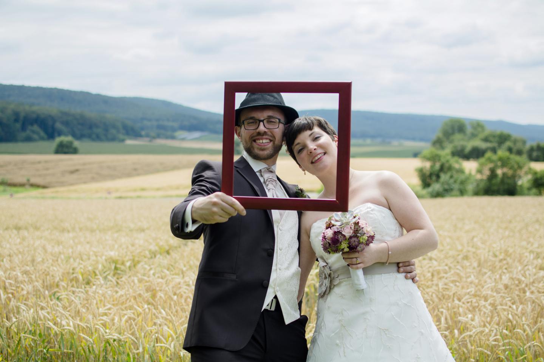 Ein Brautpaarshooting am Feldrand. Bräutigam mit Hut halt den Bilderrahmen, durch den das Ehepaar in die Kamera schaut.