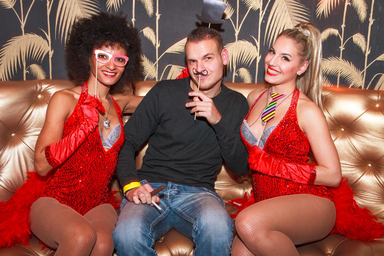 Während dem Businessevent sitzt ein Mann mit zwei in rot gekleideten Damen auf einem Sofa.