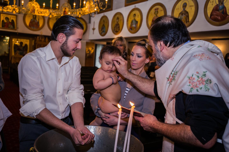 Baby mit seiner Familie bei griechisch orthodoxer Taufe