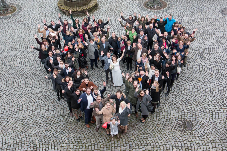 Hochzeitsgesellschaft bildet beim Hochzeitsshooting ein Herz