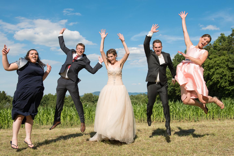 Braut, Bräutigam und die Trauzeugen springen gleichzeitig für das Gruppenfoto in die Luft.