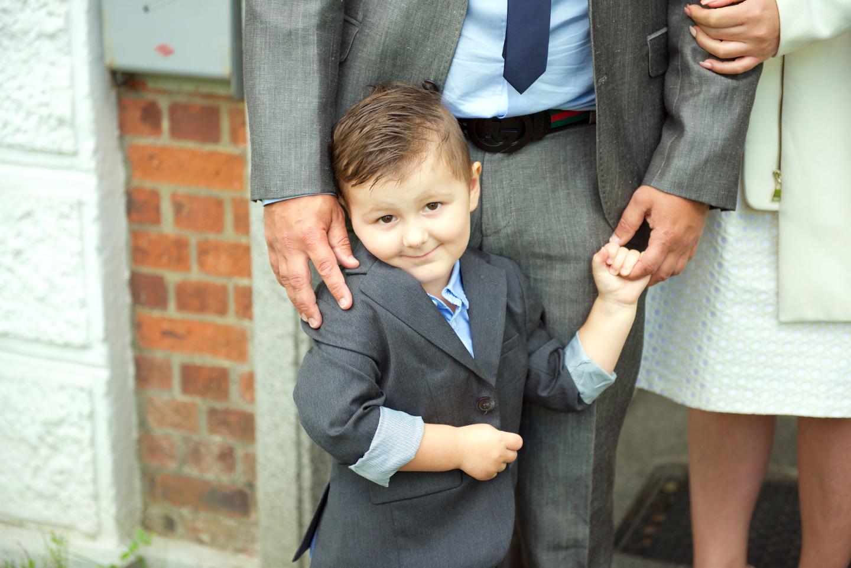 Junge blickt verlegen in die Kamera des Tauffotografen
