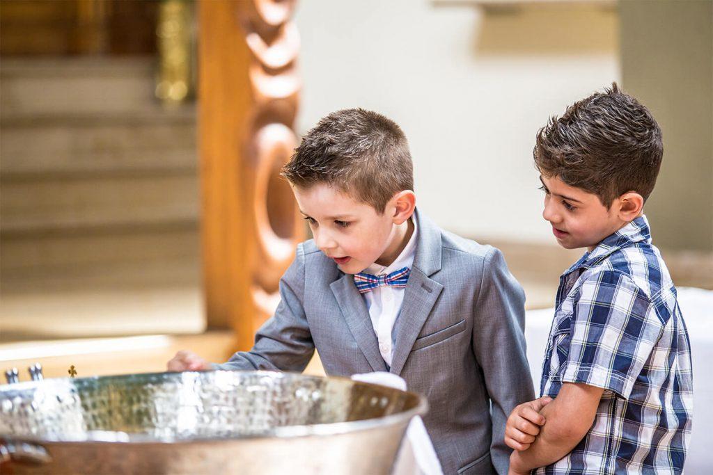 Zwei Kinder am Taufbecken.