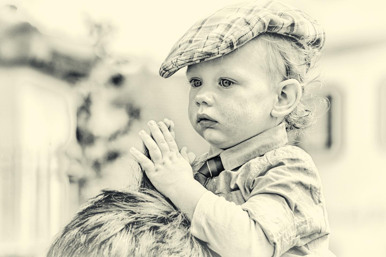 Kindershooting. Ein kleiner Junge mit Kappe sitzt auf den Schultern seines Papas.