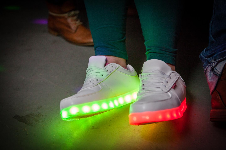 Grün und rot leuchtende Schuhe bei Dunkelheit.
