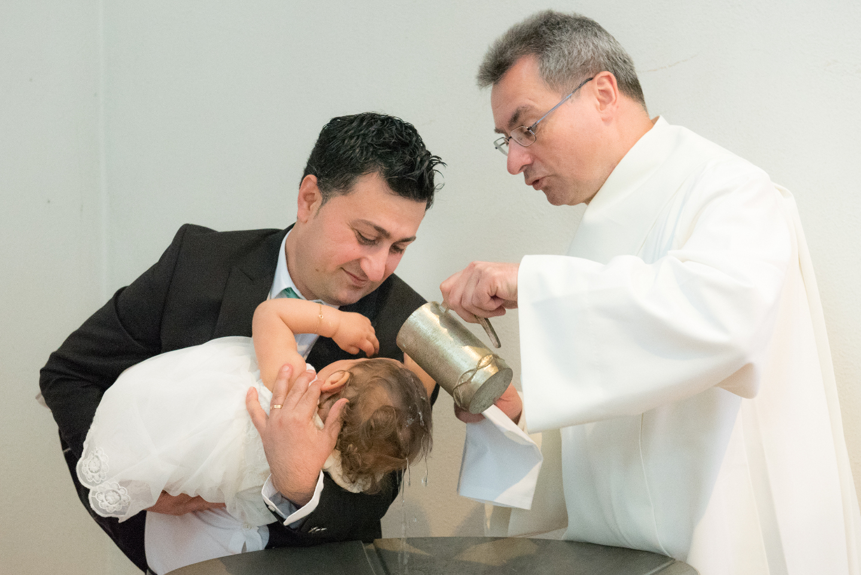 Die Taufe mit Weihwasser am Taufbecken