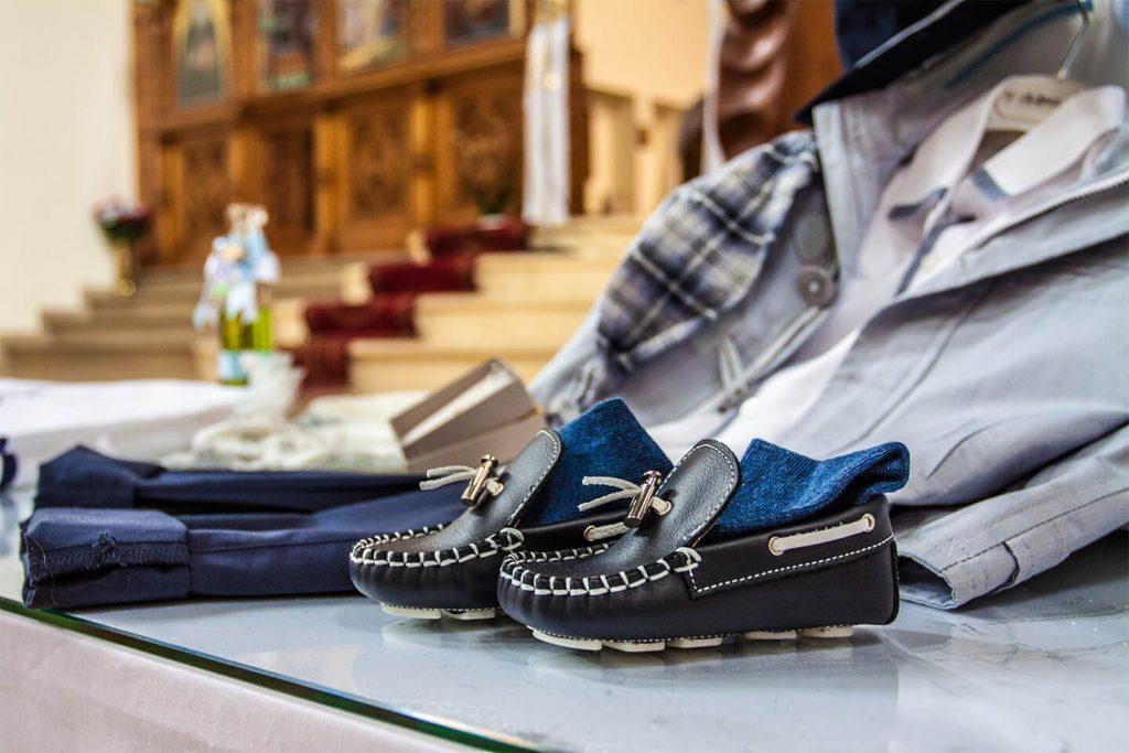 Blaue Kinderschuhe und Kinderkleidung in der Kirche