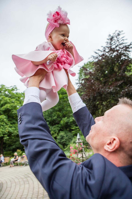 Vater hält seine tochter beim Fotoshooting für die Taufe